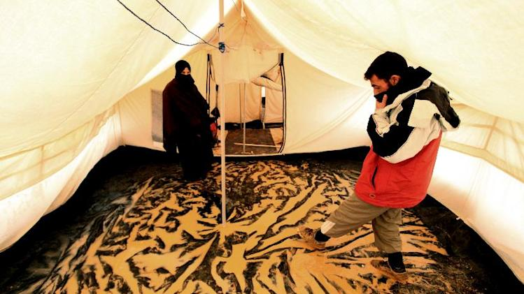 Syrian refugees stand inside their tent after a flooded hit Zaatari Syrian refugee camp, near the Syrian border in Mafraq, Jordan, Tuesday, Jan. 8, 2013. Syrian refugees in a Jordanian camp attacked aid workers with sticks and stones on Tuesday, frustrated after cold, howling winds swept away their tents and torrential rains flooded muddy streets overnight. Police said seven aid workers were injured. (AP Photo/Mohammad Hannon)