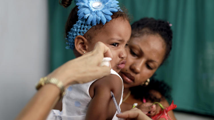 In this Aug 10, 2012 photo, a nurse gives Karolin Deniss Verdecia a shot for allergies at a government run neighborhood clinic in Havana, Cuba. Cuba's system of free medical care, long considered a birthright by its citizens and trumpeted as one of the communist government's great successes, is not immune to cutbacks under Raul Castro's drive for efficiency. The health sector has already endured millions of dollars in budget cuts and tens of thousands of layoffs, and Castro is looking for more ways to save. (AP Photo/Franklin Reyes)