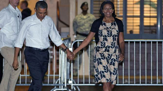 FILE - This Jan. 5, 2013 file photo shows President Barack Obama and first lady Michelle Obama preparing to board Air Force One at Honolulu Joint Base Pearl Harbor-Hickam, in Honolulu, after their holiday vacation. Michelle Obama has proven her fashion savvy time and time again since she was introduced to the country as first lady on Inauguration Day 2009. In the past four years she has adeptly walked the line between directional fashionista and everywoman. (AP Photo/Carolyn Kaster, file)