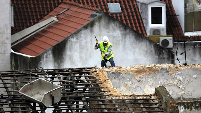 A constructions worker works on the roof of a building in Lisbon, Tuesday, Oct. 1, 2013. The eurozone's labor market appears to have stabilized, official figures indicated Tuesday, another sign that the eurozone economy is recovering from its longest-ever recession. Though Eurostat, the EU's statistics office, said the unemployment rate across the 17-member eurozone held steady at 12 percent in August, it found the number of people out of work fell for the third month running. That's the first time the region has enjoyed such a run since April 2011. (AP Photo/Francisco Seco)