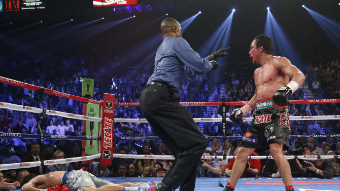 Referee Kenny Bayless, center, sends Juan Manuel Marquez, from Mexico, right, to his corner after Marquez knocked out Manny Pacquiao, from the Philippines, left, in the sixth inning of their WBO world welterweight  fight Saturday, Dec. 8, 2012, in Las Vegas. Marquez won the fight by a knockout.  (AP Photo/Eric Jamison)