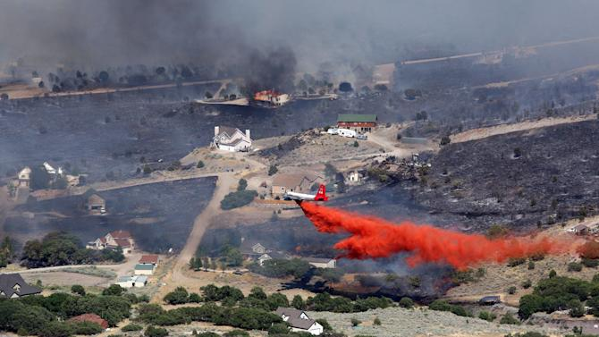 An air tanker drops retardant on a fire  after it engulfed homes in the Rose Canyon area of Herriman, Utah, Friday afternoon, June 29, 2012. Officials say the Rosecrest Fire has burned at least two homes and threatens 200 more in the foothills around Herriman, southwest of Salt Lake City. (AP Photo/The Deseret News, Ravell Call)