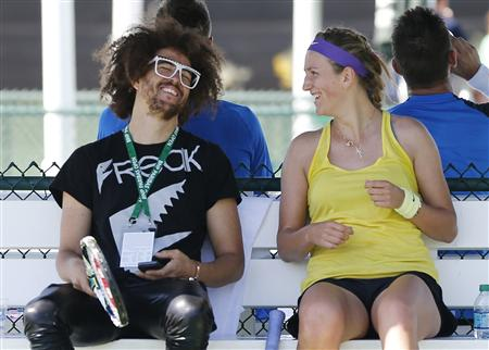 Victoria Azarenka of Belarus laughs with her boyfriend singer Redfoo during practice as she prepares for the BNP Paribas Open WTA tennis tournament in Indian Wells