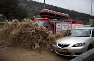 <p>A fireman's truck drives through a flooded road to rescue people trapped in their vehicles near the Israeli-Arab town of Kfar Qara in central Israel, on January 8, 2013. The worst storms in a decade left swathes of Israel and Jordan under a blanket of snow and parts of Lebanon blacked out, bringing misery to a region accustomed to temperate climates.</p>