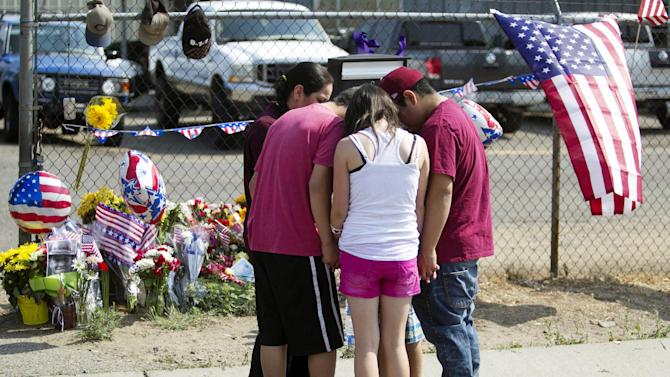The Bragg family gathers near a makeshift memorial at the fire station Monday, July 1, 2013, in Prescott, Ariz., where an elite team of firefighters was based. Nineteen of the 20 members of the team were killed Sunday when a wildfire suddenly swept toward them in Yarnell, Ariz. (AP Photo/The Arizona Republic, Patrick Breen)