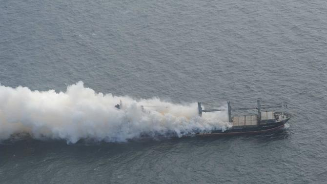 An undated handout picture obtained from the Havariekommando website shows cargo vessel Purple Beach loaded with fertilizers engulfed in smoke, west of Helgoland