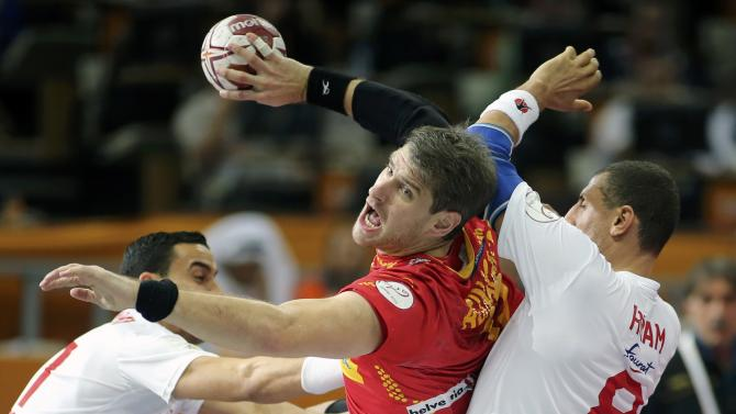 Aguinagalde of Spain is blocked by Boughanmi and Hmam of Tunisia during the round of 16 match of the 24th men's handball World Championship in Doha
