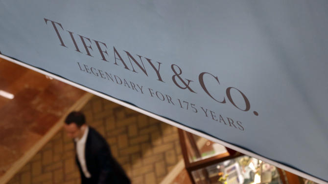 In this Tuesday, Nov. 27, 2012, photo a man walks under a banner displaying Tiffany & Co. in Boston.  Tiffany & Co. said Thursday, Nov. 29, 2012, third-quarter net income fell 30 percent, stung by a higher-than-expected tax rate, ongoing economic weakness and high precious metal and diamond costs. (AP Photo/Elise Amendola)