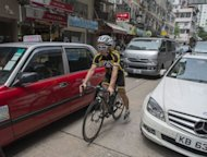 A cyclist makes his way through traffic in Hong Kong. On Hong Kong&#39;s traffic-heavy streets, horns blare as red taxis, double-decker buses and minivans shuttle people to work. But there is one thing missing -- bicycles