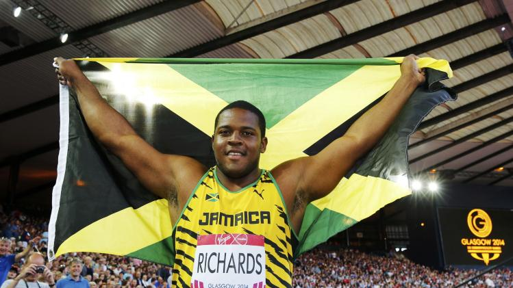 Richards of Jamaica celerbates with the flag after winning the gold medal in the men's shot put final at the 2014 Commonwealth Games in Glasgow