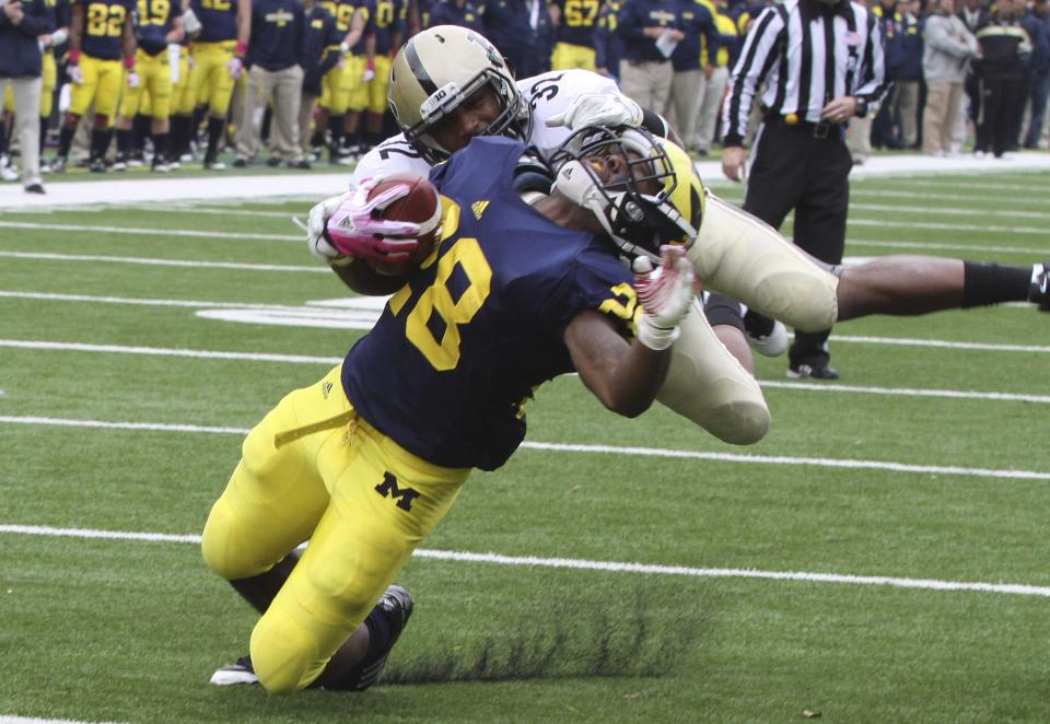 Purdue safety Albert Evans (32) tackles Michigan running back Fitzgerald Toussaint (28) before he falls into the end zone for a touchdown during the second quarter of a college football game in Ann Arbor, Mich., Saturday, Oct. 29, 2011. (AP Photo/Bill Fundaro)