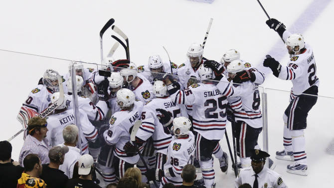 The Chicago Blackhawks mob Brent Seabrook, after his game-winning goal against the Boston Bruins during the first overtime period in Game 4 of the NHL hockey Stanley Cup Finals, Wednesday, June 19, 2013, in Boston. Chicago won 6-5. (AP Photo/Charles Krupa)