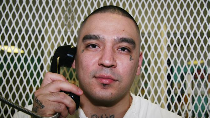 In this July 24, 2013 photo, Texas death row inmate Robert Gene Garza speaks on the phone in a visiting cage at the Texas Department of Criminal Justice Polunsky Unit in Livingston, Texas. Garza faces execution Sept. 19, 2013, for his involvement in the deaths of four women gunned down in their car in Donna in the Rio Grande Valley in September 2002. (AP Photo/Michael Graczyk)