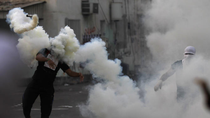 A Bahraini anti-government protester throws a tear gas canister back toward riot police who fired it during clashes after the politically charged funeral for a teenager in Muharraq, Bahrain, on Saturday, Nov. 10, 2012. Bahrain's main opposition group says the kingdom's paramilitary national guard is deploying to back up police as authorities try to quell rising political violence. (AP Photo/Hasan Jamali)