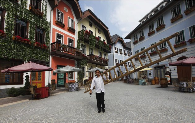 A construction worker walks with a ladder in the replica village of Austria's UNESCO heritage site, Hallstatt, in Huizhou