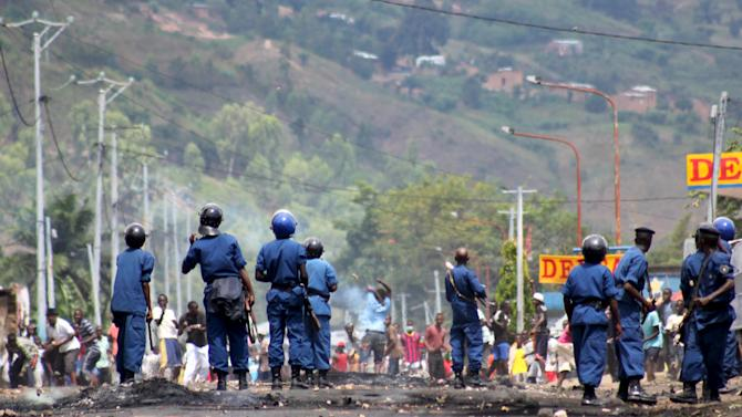 Riot policemen try to disperse protesters during a demonstration in Bujumbura