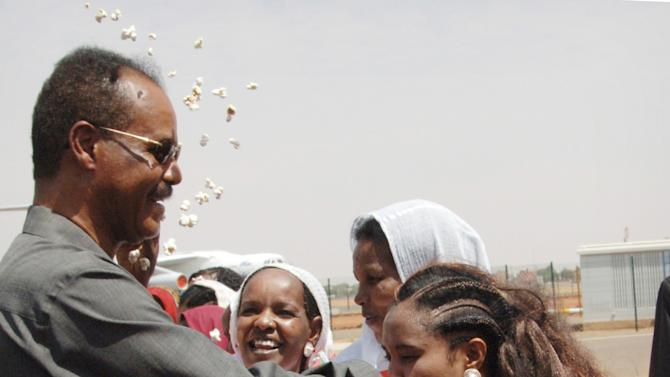 FILE - In this Wednesday, Oct. 19, 2011 file photo, an Eritrean girl kisses the hand of President Isaias Afworki, as another throws popcorn to welcome him, on his arrival at Khartoum airport in Sudan for bilateral talks between the two countries. More than 100 dissident soldiers stormed the Ministry of Information in the small East African nation of Eritrea on Monday, Jan. 21, 2013 and read a statement on state TV saying the country's 1997 constitution would be put into force, two Eritrea experts said. (AP Photo/Abd Raouf, File)