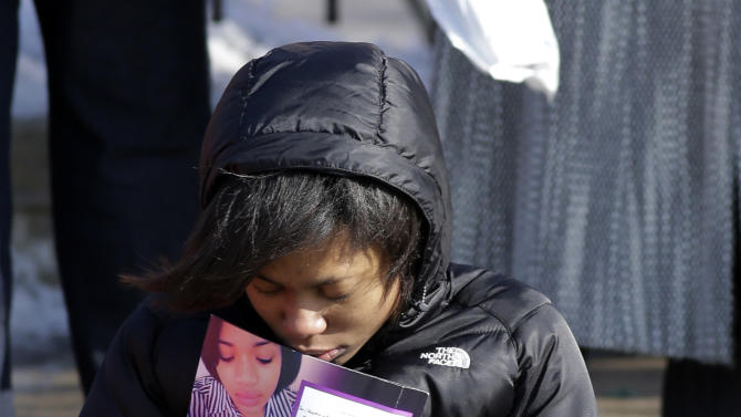 A mourner reacts as she sits outside the Greater Harvest Missionary Baptist Church during the funeral service of Hadiya Pendleton Saturday, Feb. 9, 2013, in Chicago. Hundreds of mourners and dignitaries including first lady Michelle Obama packed the funeral service Saturday for a Chicago teen whose killing catapulted her into the nation's debate over gun violence. (AP Photo/Nam Y. Huh)
