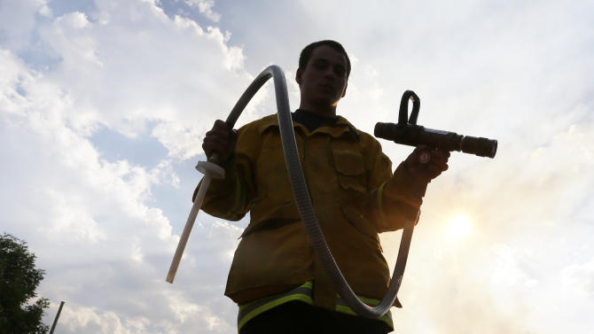 Anthony Cano a firefighter with Wildland Defense Systems Inc., demonstrates how they applied a fire retardant gel that prevents flying embers from igniting on the Waldo Canyon wildfire west of Colorado Springs, Colo., Friday, June 29, 2012.  Wildland Defense Systems Inc., is a private company that provides firefighters for insurance company Chubb Personal Insurance, one of a handful of insurance companies that send in firefighters during wildfires to protect homes as part of high-end insurance policies. (AP Photo/Chris Carlson)