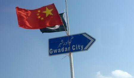 The Chinese and Pakistani flags fly on a sign along a road towards Gwadar