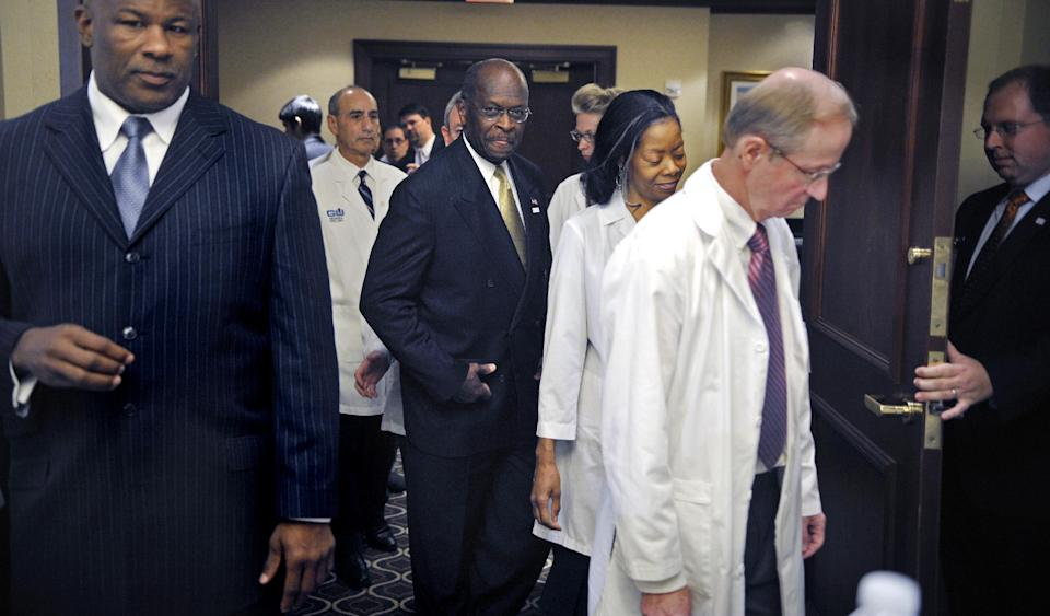 Republican presidential candidate Herman Cain, center, enters a conference room to make a statement after meeting with doctors attending the Docs4PatientCare conference in Alexandria, Va.,Wednesday, Nov. 2, 2011. (AP Photo/Cliff Owen)