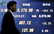A businessman walks past an electric quotation board flashing key indexes of the Tokyo Stock Exchange. A probe into insider trading has thrust the spotlight on the cosy world of Japanese share dealing, with US investment banking giant JPMorgan now ensnared in the snowballing investigation