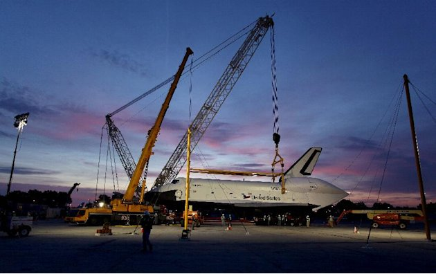 The sun rises as the space shuttle Enterprise rests on a specialized transporter after it was lifted from a NASA 747 Shuttle Carrier Aircraft at John F. Kennedy International Airport in New York, Sund