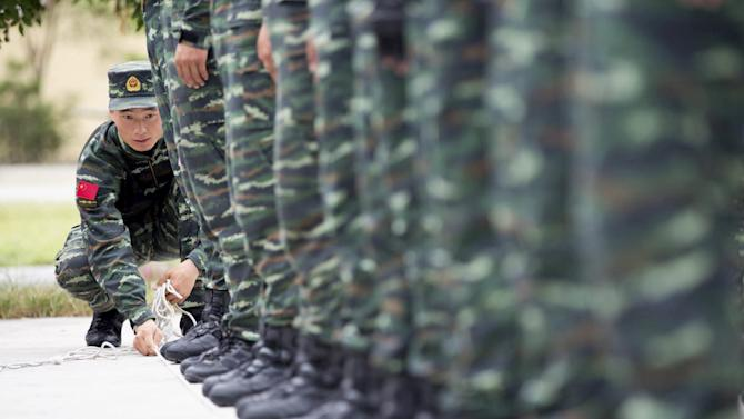 A soldier of China's People's Liberation Army uses a rope to line up other soldiers during a training session for a military parade to mark the 70th anniversary of the end of World War Two, at a military base in Beijing