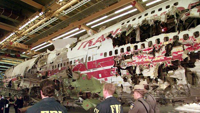 FILE - In this Nov. 19, 1997 file photo, FBI agents and New York state police guard the reconstruction of TWA Flight 800 in Calverton, N.Y. Flight 800 exploded and crashed July 17, 1996 while flying from New York to Paris, killing all 230 people aboard. Former investigators on Wednesday, June 19, 2013 called on the National Transportation Safety Board to re-examine the cause, saying new evidence points to the often-discounted theory that a missile strike may have downed the jumbo jet. (AP Photo/Mark Lennihan, File)