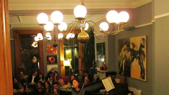 """This image taken in 2011 shows cellist and singer Helen Gillet performing in a living room show, in the Brooklyn borough of New York. """"The fans you make in a living room setting might go that extra mile for you, because you really connect,"""" said Gillet. Today, the living room show lives on, sometimes as a free exchange of talent among friends and acquaintances, other times as a hired performance. (AP Photo/John Tebeau)"""
