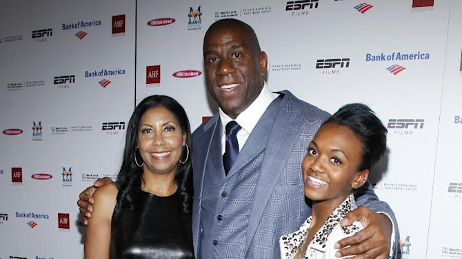 Earvin 'Magic' Johnson is poses for a photo with his wife Cookie Johnson and daughter Elisa during the premiere of ESPN Films The Announcement hosted by AHF at Regal Cinemas L.A. LIVE Stadium 14 in Los Angeles Tuesday, Mar. 6, 2011. (Joe Kohen/AP Images for AIDS Healthcare Foundation)