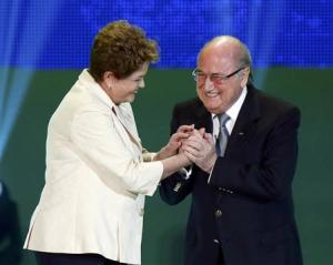 Brazilian President Dilma Rousseff and FIFA President Sepp Blatter react on stage during the draw for the 2014 World Cup at the Costa do Sauipe resort in Sao Joao da Mata