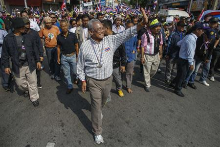 Anti-government protest leader Suthep Thaugsuban (C) waves to supporters as he marches during a rally in central of Bangkok