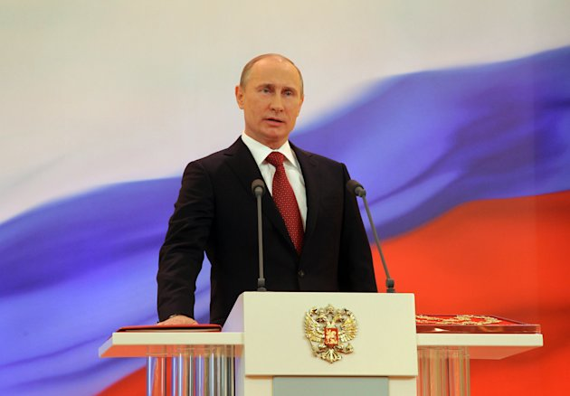 Vladimir Putin speaks with his hand on the Constitution during his inauguration ceremony as new Russia's president in Moscow Monday, May 7, 2012.  Putin has been sworn in as Russia's president for a t