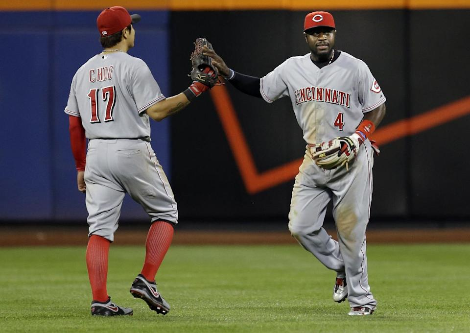 Cincinnati Reds' Shin-Soo Choo, left, celebrates with Brandon Phillips after Phillips caught a fly ball hit by New York Mets' David Wright during the fifth inning of the baseball game at Citi Field Monday, May 20, 2013 in New York. (AP Photo/Seth Wenig)