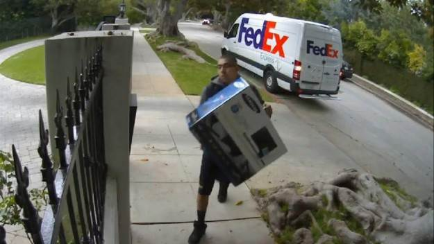 Viral Video: FedEx delivery man throws computer monitor over fence