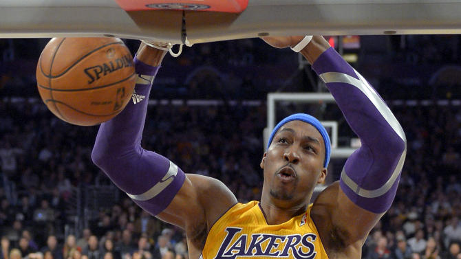 FILE - In this Jan. 25, 2013 file photo, Los Angeles Lakers center Dwight Howard dunks during the first half of their NBA basketball game against the Utah Jazz, in Los Angeles. Chris Paul is staying in Los Angeles; Dwight Howard could be leaving. NBA free agency opens, with Paul sticking with the Clippers and Howard exploring his options before deciding on his future with the Lakers. (AP Photo/Mark J. Terrill, File)
