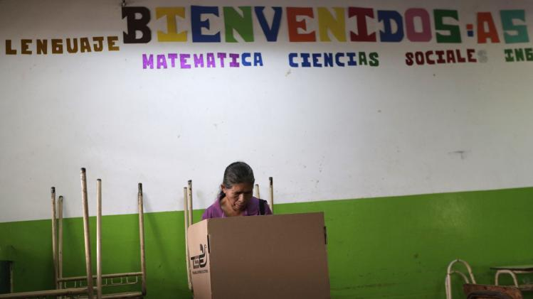 A woman prepares to cast her ballot in a presidential election runoff at a polling station outside in San Salvador