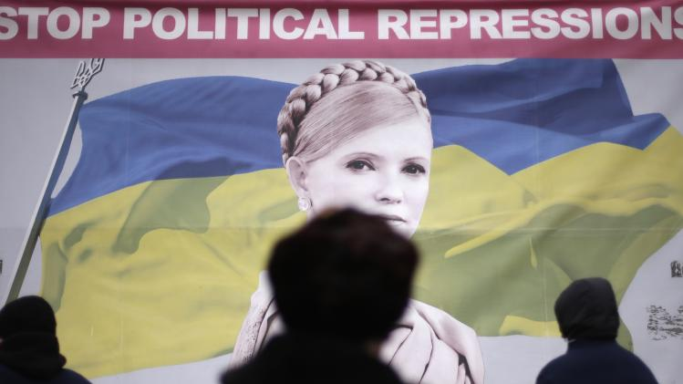 People walk by poster of jailed former Ukrainian PM and opposition leader Tymoshenko at Independence Square in Kiev