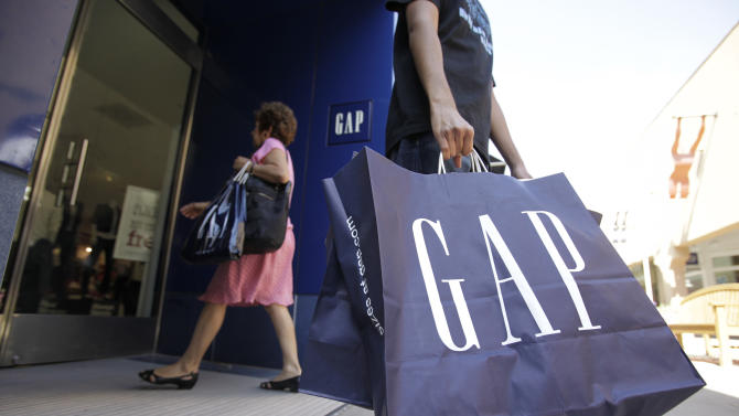 FILE - In this Aug. 9, 2009, file photo, a shopper leaves a Gap store in Palo Alto, Calif. The nation's largest clothing chain, which operates, Gap, Old Navy, Banana Republic and Athleta, said it would raise the wages to $10 by 2015. (AP Photo/Paul Sakuma, File)