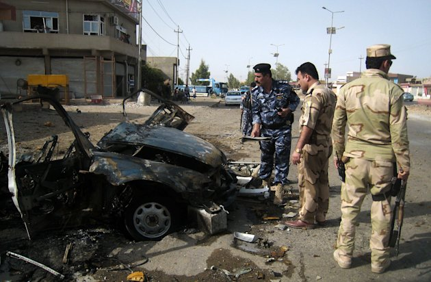 Security forces inspect the scene of a car bomb attack in Kirkuk, 290 kilometers (180 miles) north of Baghdad, Iraq, Thursday, Aug 16, 2012. Five separate bombings in central and northern Iraq, killed and wounded scores of people early Thursday, police said. (AP Photo/Emad Matti)