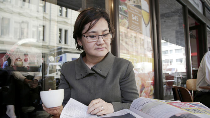 "Agnes Lee, 52, an IT consultant, reads a paper while having a coffee in Sydney, Thursday, Sept. 5, 2013. The ruling Labor Party's probable collapse in Australia's next election is largely the consequence of its qualified success in the last one three years ago. To form the coalition she needed to stay in power, then-Prime Minister Julia Gillard reneged on a promise and agreed to place a carbon tax on major polluters. ""The Labor government is all about themselves - the individual - rather than the whole party,"" said Lee who plans to vote for the conservative coalition on Saturday. (AP Photo/Rick Rycroft)"