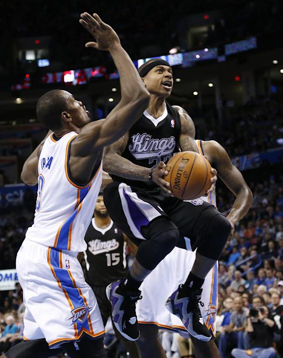 Sacramento Kings guard Isaiah Thomas (22) drives between Oklahoma City Thunder forward Serge Ibaka (9) and center Kendrick Perkins (5) in the second quarter of an NBA basketball game in Oklahoma City,