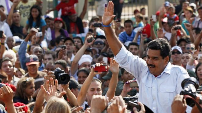 Maduro greets supporters as he leaves a polling station after voting in the presidential election in Caracas on April 14.