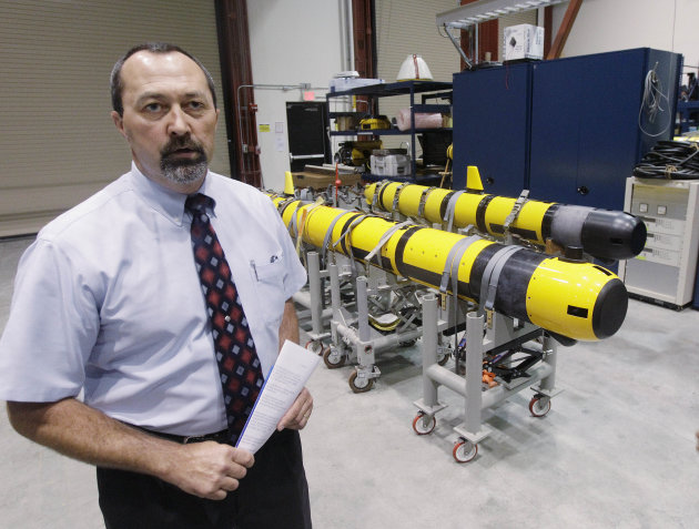 Christopher Egan, an unmanned systems customer advocate, stands near a pair of unmanned underwater vehicles (UUV) in a lab at the Naval Undersea War Center in Middletown, RI., Tuesday, July 31, 2012.