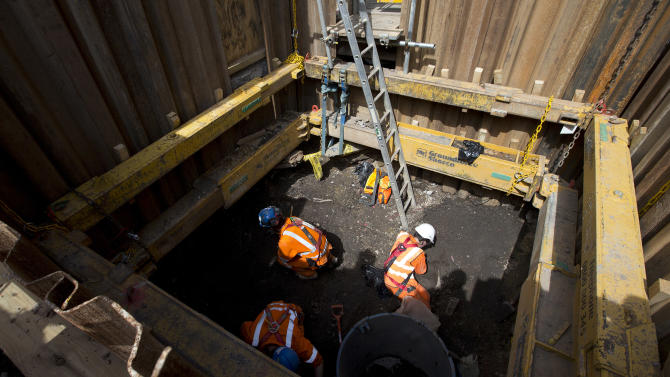 In this Wednesday, Aug. 7, 2013 photo, bones and and artefacts are uncovered by archaeologists digs on a site near London's Liverpool Street railway and tube station during the building of the new hi-speed rail line, during a media visit in London. Commuters scuttling past London's Liverpool Street rail and subway station this week were unaware that just feet away, archaeologists were gently unearthing the centuries-old bones of some previous Londoners. Jewelry, pieces of ships, medieval ice skates, centuries-old skulls _ some incredible pieces of London's history aren't in museums, they're underground. More often than not, they stay there, but work on a new railway line under the British capital is bringing centuries of that buried history to light. The 118-kilometer (73-mile) Crossrail line is Britain's biggest construction project and the largest archaeological dig in London for decades. In the city's busy business core, archaeologists have struck pay dirt, uncovering everything from a chunk of Roman road to dozens of 2,000-year-old horseshoes, some golden 17th-century bling _ and the bones of long-dead Londoners. (AP Photo/Alastair Grant)