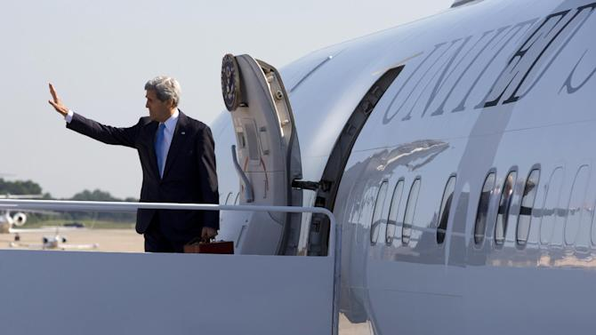 Secretary of State John Kerry waves as he boards his plane at Andrews Air Force Base, Md., Friday, June 21, 2013, en route to Doha, Qatar. Kerry began an overseas trip plunging into two thorny foreign policy problems facing the Obama administration: unrelenting bloodshed in Syria and efforts to talk to the Taliban and find a political resolution to the war in Afghanistan. (AP Photo/Jacquelyn Martin, Pool)