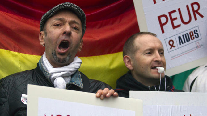People demonstrate for equal rights with placards and flags in Paris, France, Wednesday, April 10, 2013. A gay rights watchdog group says that the number of reported homophobic acts has risen in France in recent weeks, amid nationwide protests over a bill under parliamentary debate that would legalize gay marriage. The group staged a demonstration Wednesday night for equal rights for gays. The Senate approved the amendment involving gay marriage Tuesday. The Senate is expected to approve the overall bill later this week. Placards reads, 'Our love is stronger, and 'We forget nothing'. (AP Photo/Jacques Brinon)