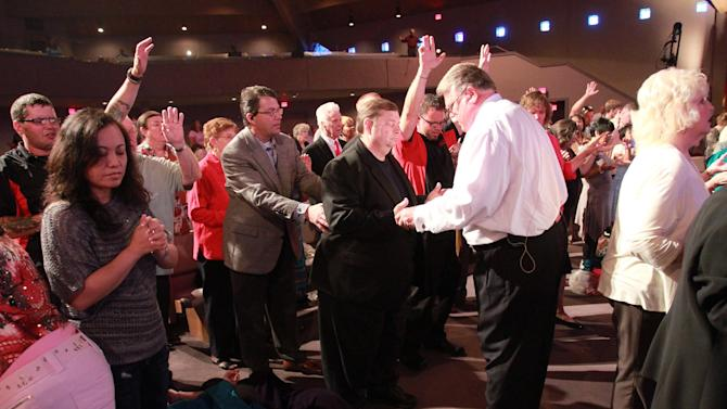 In this March 25, 2012, photo, Brownsville Assembly senior pastor Rev. Evon Horton prays with an churchgoer as he performs the practice of the laying of hands on members of the congregation in Pensacola, Fla. The church that was home to the largest Pentecostal outpouring in U.S. history is on the edge of financial ruin. The revival that drew some 5,500 people nightly at its height saddled the congregation with an $11.5 million debt that members were left to pay off after both the out-of-town throngs and former Rev. John Kilpatrick moved on. The red ink is mostly unknown outside the congregation. (AP Photo/John David Mercer)