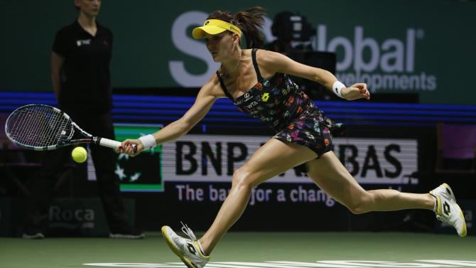 Agnieszka Radwanska of Poland hits a return to Simona Halep of Romania during their WTA Finals singles semi-final tennis match at the Singapore Indoor Stadium